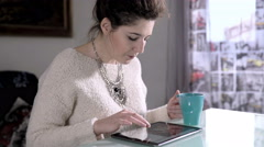 Charming woman drinks hot coffee using tablet Stock Footage