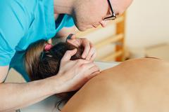 Doctor is examing his patient neck. Close up - stock photo
