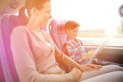 happy family with tablet pc sitting in travel bus - stock photo