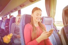 happy woman sitting in travel bus with smartphone - stock photo