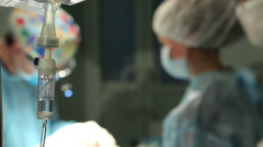 Intravenous dropper in surgical room. Surgical team operating - stock footage