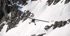 Hi Wing Bush Plane With Skis Flying Past Avalanche Cliffs and Crags Stock Footage