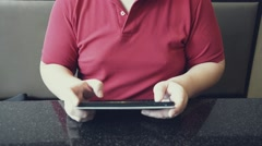 Chubby Asian male in red shirt use tablet with touch screen - stock footage
