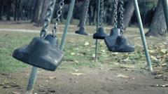 Empty Swings swing with wind in a empty park Stock Footage