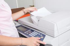 Close up of a young secretary using a copy machine Stock Photos