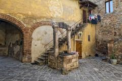 Tuscany san quirico medieval houses with water well Stock Photos