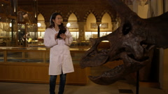4K Scientist in museum standing next to dinosaur & looking at computer tablet Stock Footage