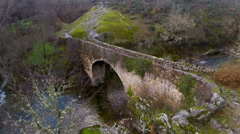 Aerial view of a river on a mountain, with an old bridge. Stock Footage