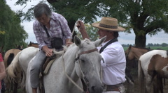 Gaucho helps Asian tourist mount horse, Argentina, pampas area Stock Footage