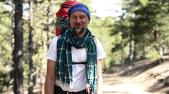 Bearded smiling hiker with a backpack - stock footage