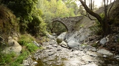 Small mountain river flows under the medieval Venetian bridge Stock Footage