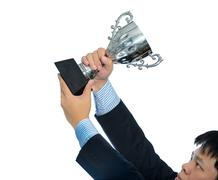 Businessman holding a champion silver trophy on white background - stock photo