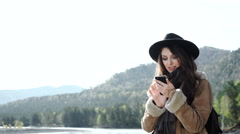 Woman on her mobile phone while searching interesting places in mountains Stock Footage