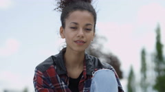 Portrait of a young african american woman wearing checkered shirt, outdoors. - stock footage