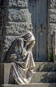 Widow while weeping marble statue outside a tomb cemetery Stock Photos