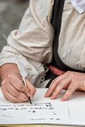 Hands while writing a letter with a plume Stock Photos