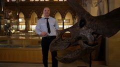 4K Portrait of funny security guard standing next to dinosaur skeleton in museum Stock Footage