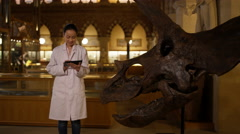 4K Scientist in museum standing next to dinosaur & looking at computer tablet - stock footage