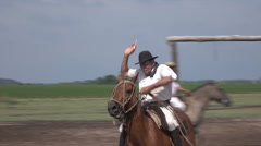 Gaucho demonstrates ring lancing contest on horseback, Argentina ranch - stock footage