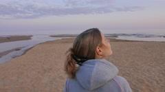 Dreamy young woman enjoying sun on the beach. Northern baltic seascape. 4K UHD - stock footage