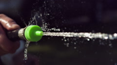Water from garden hose sprayed out of nozzle slow motion Stock Footage