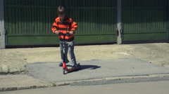 Boy riding scooter Stock Footage