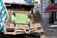 Green rubbish container in a rubbish truck Stock Photos