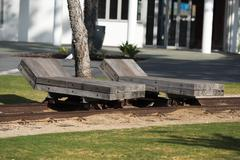 solid wooden chaise longue on rail tracks - stock photo
