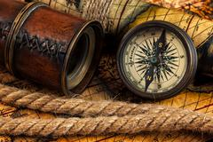 Old vintage compass and navigation instruments on ancient map Stock Photos