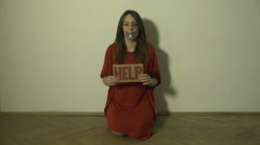 Beaten woman with bruise on eye kneeling and raising message on cardboard - HELP Stock Footage