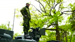 Military soldier standing on tank during a practice maneuver of the Swedish army - stock footage