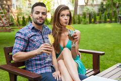 Couple sitting on the bench with drinks and spending great time. Positive emo Stock Photos