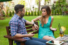 Couple sitting on the bench in the garden and arguing. Stock Photos