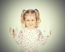Little girl holding filter for drinking water and  glass of clean water. - stock photo