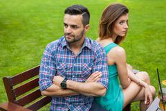 Couple sitting on the bench in the garden. They are taking offense and sittin Stock Photos