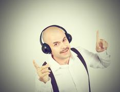 mustache businessman listening to music on headphones and sings - stock photo