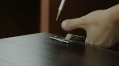 The worker is fastening the door hinge to the furniture detail using screwdriver Stock Footage
