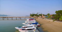 Speedboats Moored On Tropical Beach Overhead Aerial Flyover Shot Stock Footage