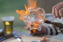 Glass working hands while blowing with fire a piece of art Stock Photos