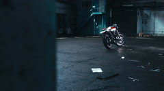 Dolly shot of a custom cafe racer motorcycle standing in the large warehouse Stock Footage