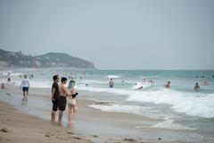 LOS ANGELES, USA - AUGUST 3, 2014 - people on Zuma sandy  beach in summer tim Stock Photos