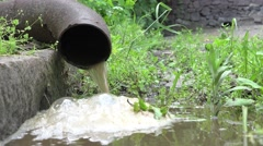 Sewage flow from the rusty iron pipes on the green grass Stock Footage