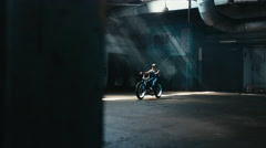 Young Caucasian male in denim overalls riding custom made bicycle in warehouse - stock footage