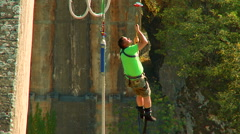 Bungee Jumping. Guy hanging on the rope next to the bridge Stock Footage