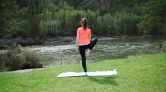 Practicing yoga in the morning, mountains and sun ray in the background. - stock footage