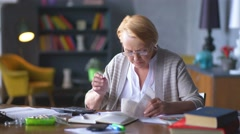 Elderly woman worries about bills. she considers on calculator and gets upset Stock Footage