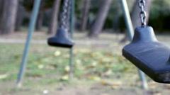 Empty swings swing in a desolate park Stock Footage