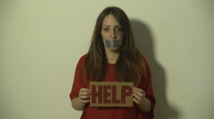 Beaten girl raising message with HELP inscription, tilt up to face with bruises. - stock footage