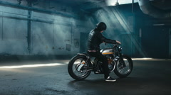 Young male biker in leather jacket driving  custom motorcycle in large warehouse Stock Footage