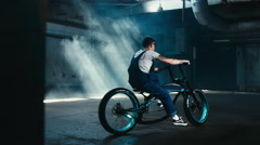 Young male in denim overalls riding custom bicycle in large warehouse garage - stock footage